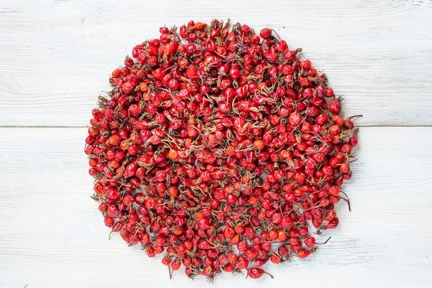 Ягоды шиповника на белом фоне деревянных, плоды красного шиповника.