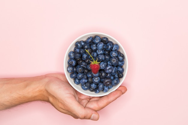 Berries on a pink surface. view from above. blueberries in a white bowl on a pink surface with hands. holding blueberries with both hands. vitamins concept