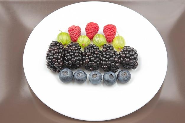 Berries raspberries, blueberries, gooseberries and blackberries on a white plate. useful vitamin healthy food fruit. healthy vegetable breakfast
