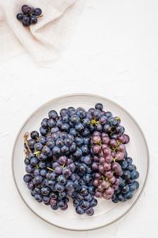 Berries of ripe blue grapes on a plate on a table harvesting in autumn top view