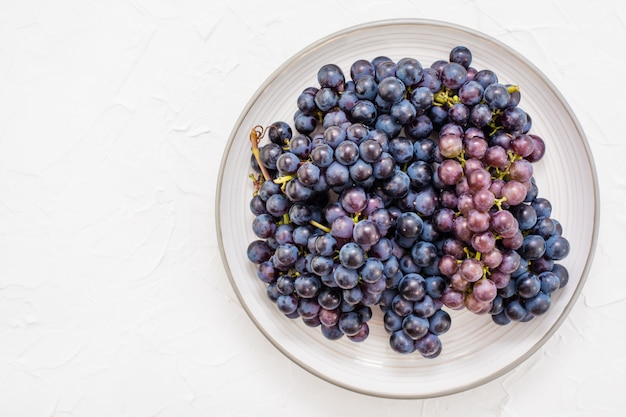 Berries of ripe blue grapes on a plate on a table top view