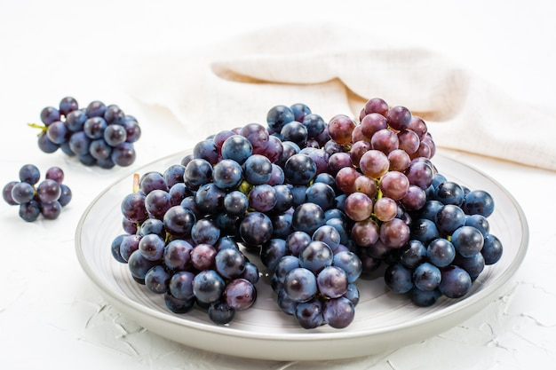 Berries of ripe blue grapes on a plate on a table