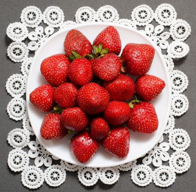 Berries ripe strawberries on the plate on lace napkin, top view, gray