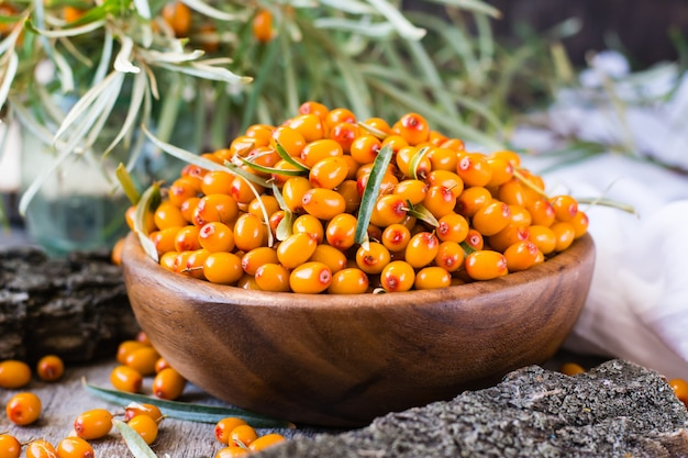 Berries of sea-buckthorn in a bowl on a wooden table