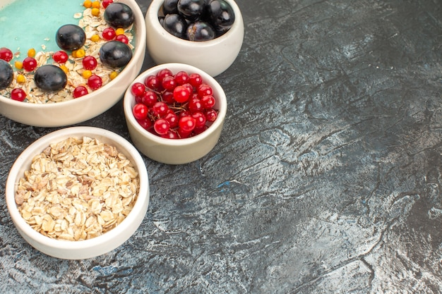 Ягоды белые чаши овсяных хлопьев, винограда и красной смородины на сером столе