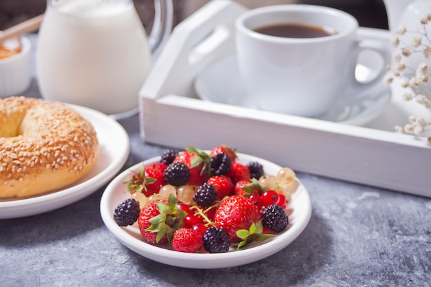 Berries on the white plate, bagel, cup of coffee and honey for breakfast.