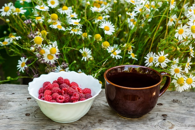 Berries on a wooden background with flowers.