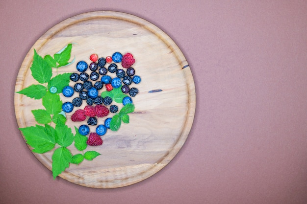 Berries on a wooden plate. composition of three types of summer berries lying on a textured wooden plate. top view on a wooden plate filled with many berries. wild berries.
