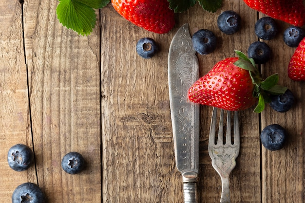 Berriey mix, blueberry, strawberry on wood background with vintage, styled fork and knife.