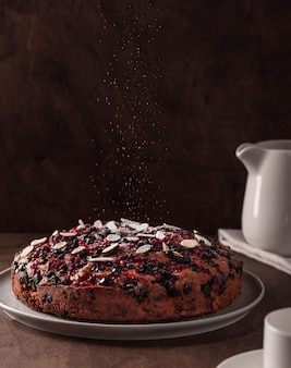 Berry cake dusted with icing sugar on a dark background