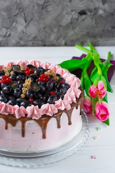 Berry cake with cream, grapes, red currant, white currant. pink tulips.