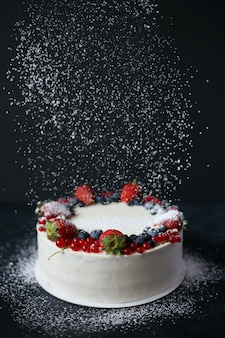 Berry cake with icing sugar on dark table