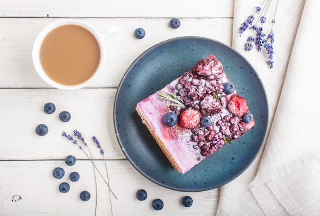 Berry cake with milk cream and blueberry jam on blue ceramic plate with cup of coffee and fresh blueberries. top view.