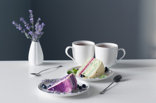 Berry cheesecakes and two cups of tea on  white table on background gray wall