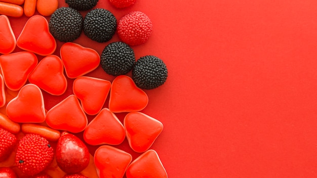 Berry fruit and heart shape candies on red background