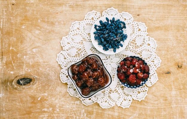 Варенье из ягод на красивой салфетке на деревянном фоне