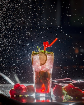 Berry lemon cocktail with red pipe and ice cubes in black starry background.