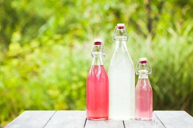 屋外のテーブルの上のボトルのベリーレモネード