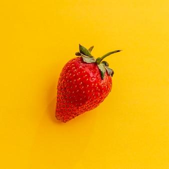 Ягода красная зрелая клубника на яркой желтой предпосылке. крупный план. вид сверху.