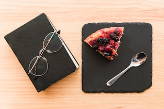 Berry pastry near diary and spectacles on wooden desk