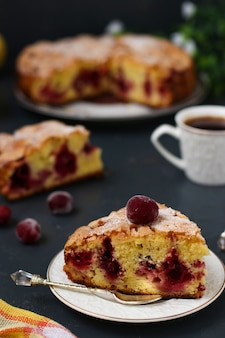 さくらんぼのベリーパイは、暗い背景のプレートにあります。手前にはケーキとコーヒーがあります