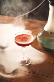 Berry red cocktail with foam in a glass and smoking hookah.