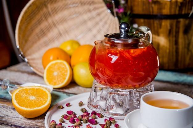 Ягодный чай из облепихи в стеклянном чайнике в кафе