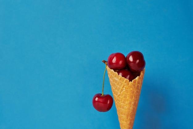 Berry season. ice cream cone with cherries on blue background
