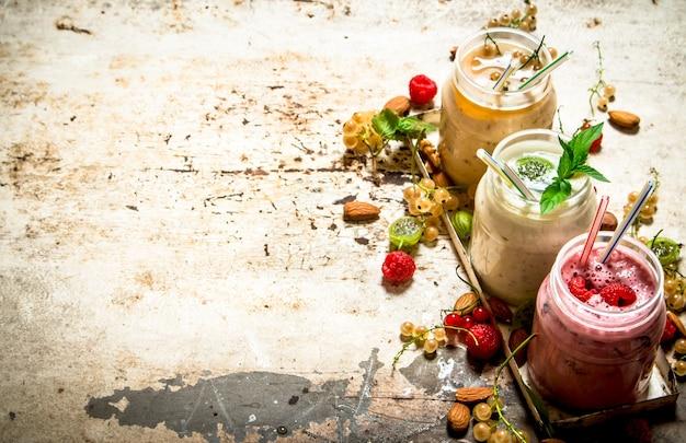 素朴なテーブルにナッツを添えたスグリ、グーズベリー、ラズベリーから作られたベリーのスムージー。