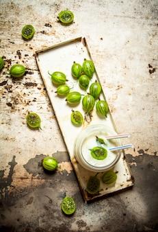 素朴なテーブルの上に緑のグーズベリーから作られたベリーのスムージー。