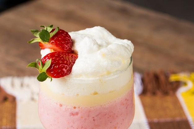 신선한 딸기와 라스베리와 냉동 요구르트를 섞어 만든 키 큰 잔에 담긴 베리 스무디 또는 밀크 쉐이크