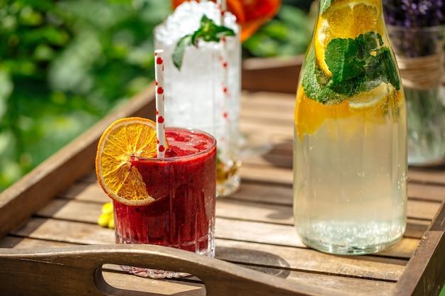 Ягодный смузи с лимонадом и коктейлями на деревянном подносе
