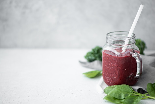 Berry smoothie with spinach and chia seeds in a glass mug