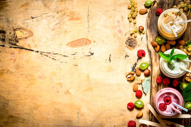 Berry smoothie with wild berries and nuts on wooden background.