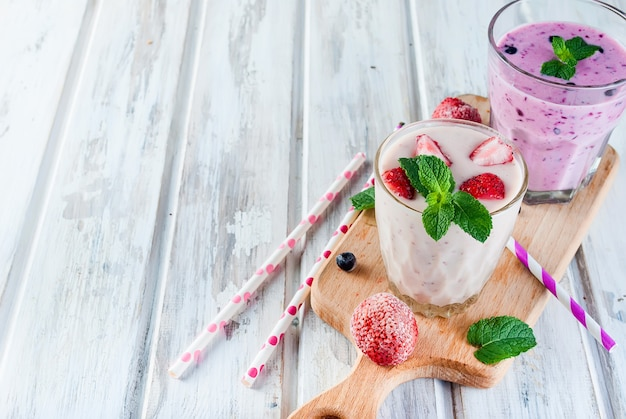 Berry smoothies of strawberries, banana and blueberries in glasses and ingredients on a wooden table