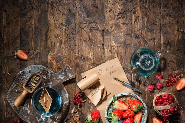 ベリーの静物。ベリー、お茶、ペン、カレンダー、古い茶色の木製テーブルのノート、上面図