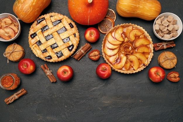 Ягодный пирог и яблочный пирог на черном фоне с яблоками и специями