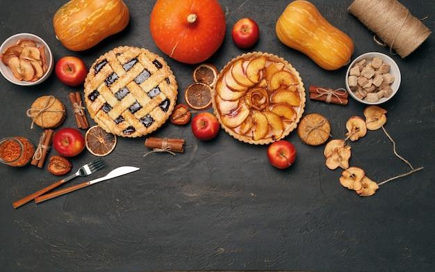 Ягодный пирог и яблочный пирог на черном с яблоками и специями