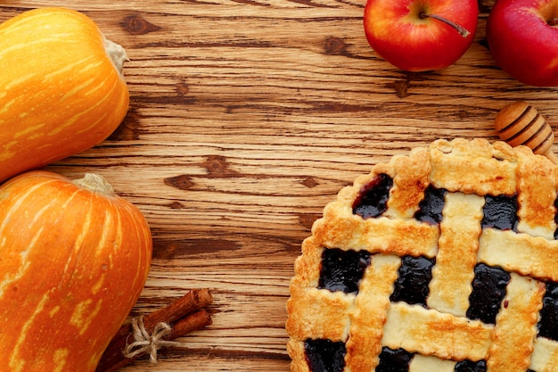 Ягодный пирог и апельсиновая тыква на деревянном столе крупным планом
