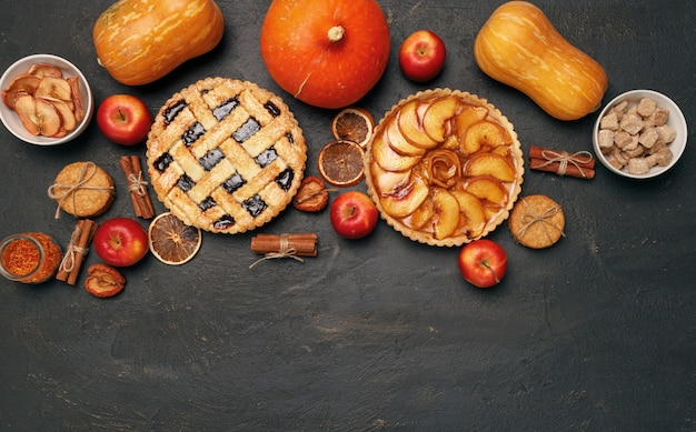 Berry tart pie and apple tart pie on black background with apples and spices