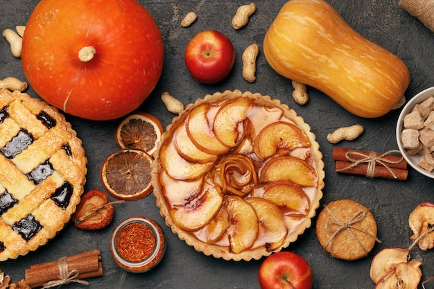 Berry tart pie and apple tart pie on black table with apples and spices