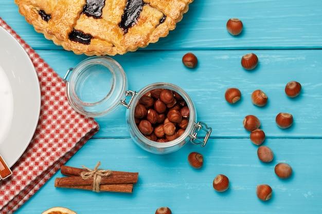 青い木製の背景の上面図にベリーのタルトパイ