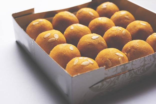 Besan laddoo - 구운 그램 가루에 desi ghee 및 설탕을 섞어서 맛있고 둥근 모양의 달콤한 laddu를 만듭니다. 그릇에 제공됩니다. 선택적 초점