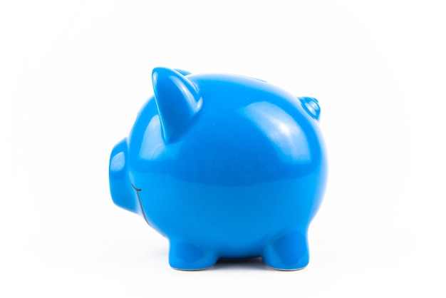 Beside blue piggy bank on white background. finance savings and money wealth concept.