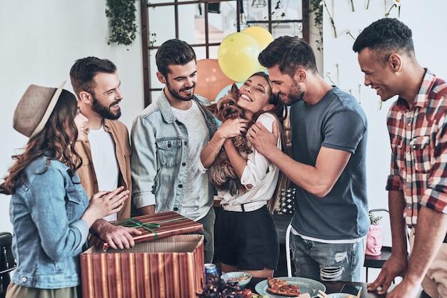 Лучший сюрприз на день рождения. счастливая молодая женщина держит щенка и улыбается