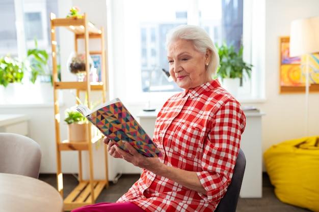 Лучшая книга. радостная пожилая женщина улыбается, наслаждаясь интересной историей