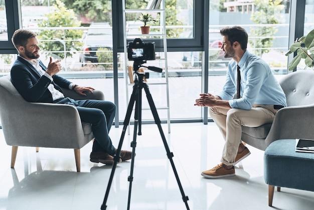 최고의 비즈니스 브이로그. 스마트 캐주얼 차림의 두 젊은이가 실내에서 새 비디오를 만드는 동안 이야기하고 있습니다.