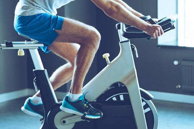 Best cardio workout. side view part of young man in sportswear cycling at gym