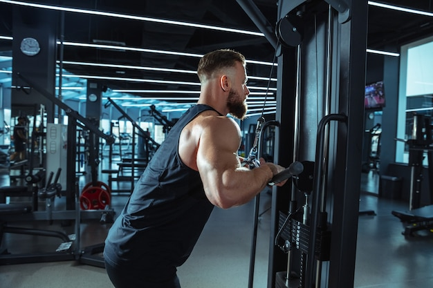 Best choice. young muscular caucasian athlete training in gym, doing strength exercises, practicing, work on his upper body with weights and barbell. fitness, wellness, healthy lifestyle concept.