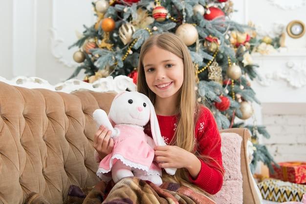 최고의 크리스마스 장난감. 크리스마스 트리에서 귀여운 토끼와 어린 소녀입니다. 작은 소녀 잡고 토끼 장난감. 어린 아이가 부드러운 장난감을 가지고 노는 것입니다. 현재와 함께 행복 한 미소 작은 아이. 가장 기대되는 장난감.